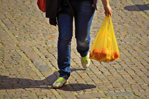 person walking, carrying plastic shopping bag with fruit